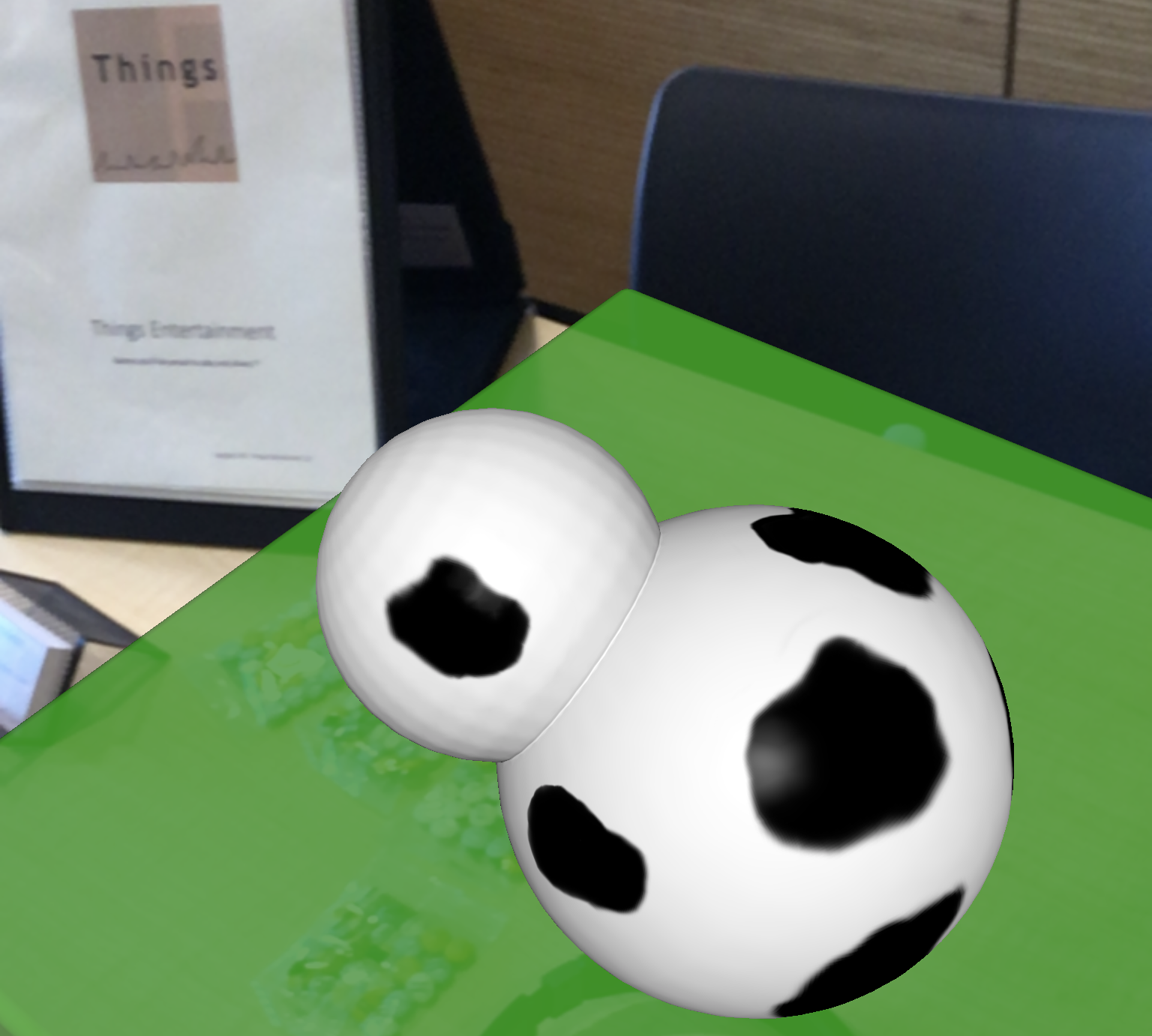 View of a table through an augmented reality application. The table has been augmented with a green field and a demo cow. The green field is semi-transparent, so you can still see other items on the table through the field. The demo cow, though, is opaque.